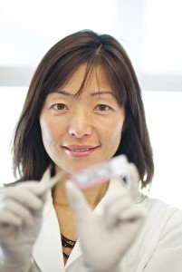 Model released photo of an Asian immunobiologist with a forceps, looking at a glass slide of virus infected skin tissue